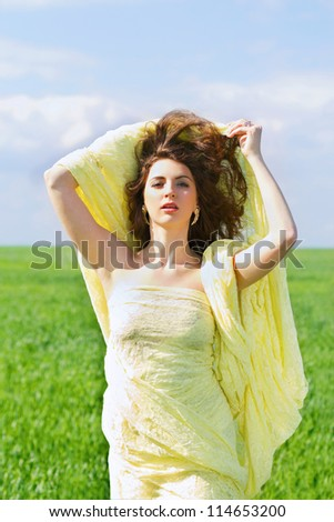 Portrait of a attractive young woman wrapped in yellow cloth - stock photo