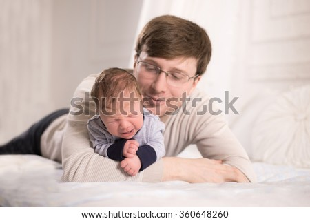 Portrait of a baby and a young man with glasses