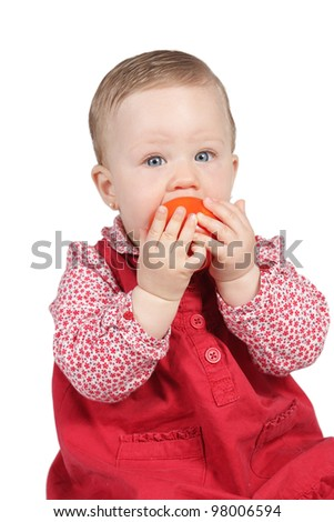 Portrait of a baby dressed in red with tomato in the hands