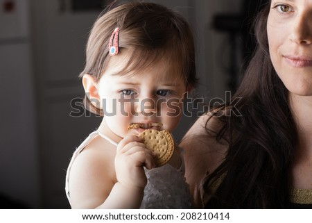 portrait of a baby girl eating a biscuit dressed in white - stock photo
