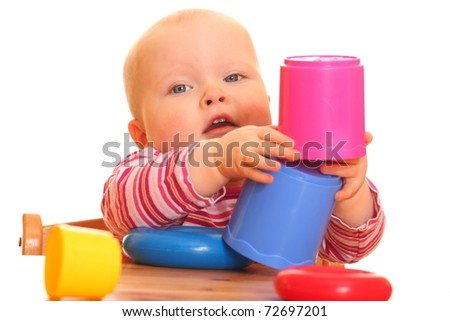 Portrait of a baby girl playing with a toy pyramid