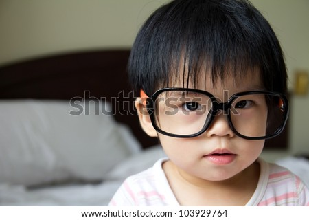 Portrait of a baby girl wearing big spectacles - stock photo