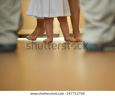 Portrait of a baby learning to walk with help from mother and father - low angle - stock photo