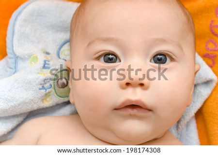 Portrait of a baby of 3 months on orange background after leaving the bath - stock photo