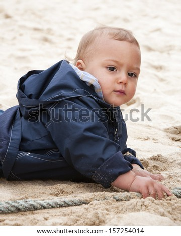 Portrait of a baby or a toddler child, crawling on a sand beach and playing with a rope. - stock photo
