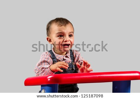 Portrait of a baby sitting on a red table crying - stock photo