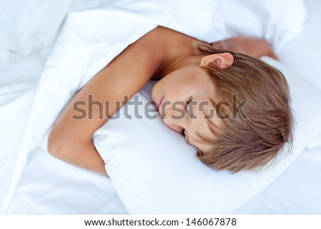 Portrait of a baby sleeping on a white pillow and blanket - stock photo
