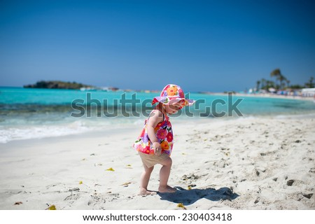 Portrait of a baby walking by the sea - stock photo