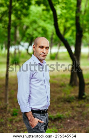 Portrait of a bald and brutal man in the park