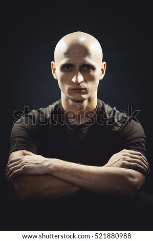 Portrait of a bald shaven men on a black background