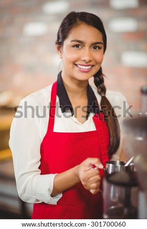 Portrait of a barista steaming milk at the coffee shop - stock photo