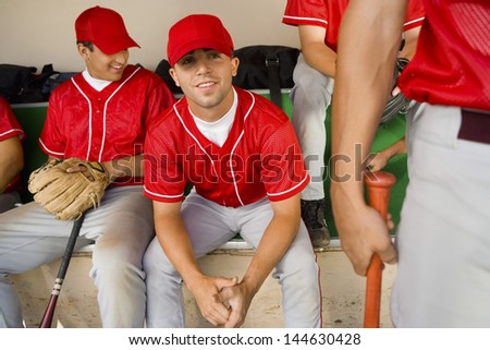 Portrait of a baseball player with team mates sitting in the dugout - stock photo