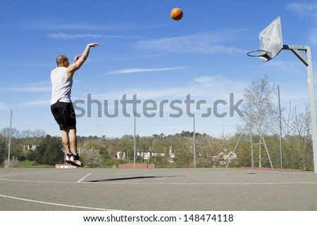 Portrait of a Basketball player taking a jump Shot on an outdoor basketball court - stock photo