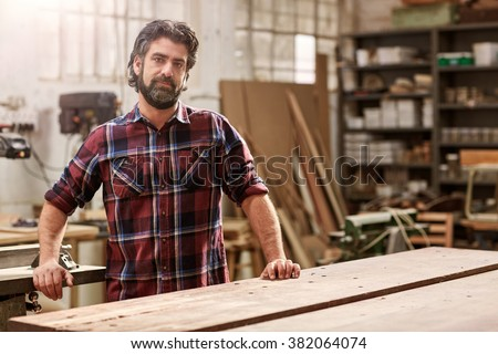 Portrait of a bearded craftsman standing proudly in his woodwork studio, where he runs and artisan workshop, with shelving and many pieces of wood behind him - stock photo