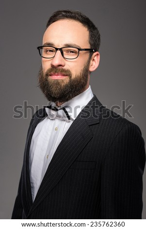 Portrait of a bearded man in a suit and a tie who is posing over grey background.
