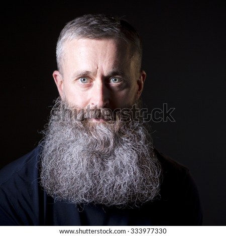 Portrait of a bearded man on a black background looking into camera