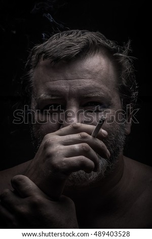 Portrait of a bearded man. Smokes. Toned.
