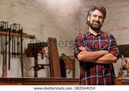 Portrait of a bearded man who owns a small carpentry business, standing in his workshop with with arms folded and showing strong forearms, smiling confidently at the camera - stock photo