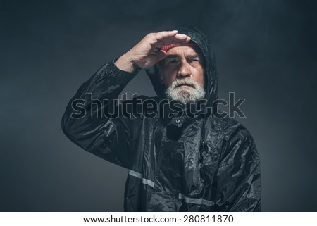 Portrait of a Bearded Middle Age Man with Facial Hair, Wearing Black Rain Jacket, Looking Afar with a Serious Facial Expression. - stock photo