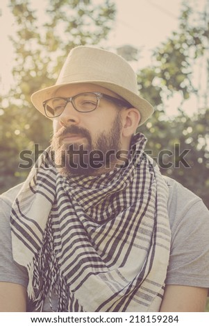 Portrait of a bearded young hipster man daydreaming, looking away. Retro tones - stock photo