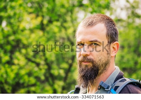 Portrait of a bearded young man with backpack with green trees in the background.