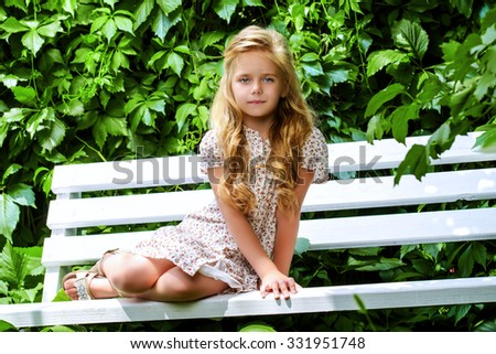 Portrait of a beauiful little girl smiling to sunny summer day. - stock photo