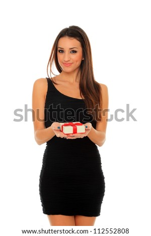 Portrait of a beautiful adult woman in black dress holding a gift box posing over white background - stock photo