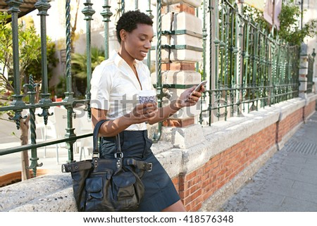 Portrait of a beautiful african american business woman holding a take away coffee mug, using a smart phone in city outdoors, smiling. Professional black woman technology in city, sunny exterior. - stock photo