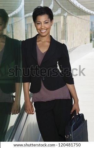 Portrait of a beautiful African American business woman leaning on glass - stock photo