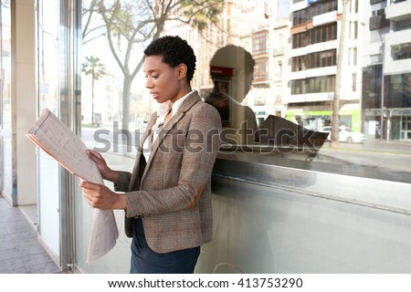 Portrait of a beautiful african american business woman reading the financial paper stock market with reflective glass office building, sunny outdoors. Professional black woman, finance city exterior. - stock photo