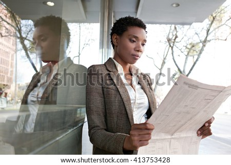 Portrait of a beautiful african american business woman reading the financial paper stock market by reflective glass office building, sunny outdoors. Professional black woman in finance city exterior. - stock photo