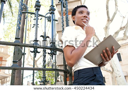 Portrait of a beautiful african american business woman taking notes in a classic city with architectural features, sunny exterior. Professional black woman working in financial district, outdoors. - stock photo