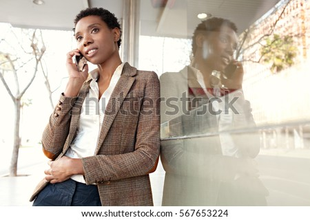 Portrait of a beautiful african american business woman with office building glass city reflections, smiling outdoors. Professional black woman in smart phone conversation call, lifestyle technology.