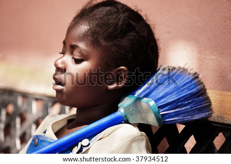 portrait of a beautiful African girl holding a blue broom - stock photo