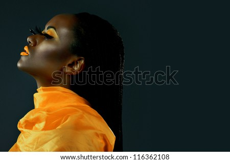 Portrait of a beautiful African girl with creative make-up in profile - stock photo