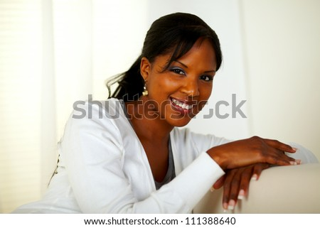 Portrait of a beautiful afro-American woman smiling at you at soft colors composition