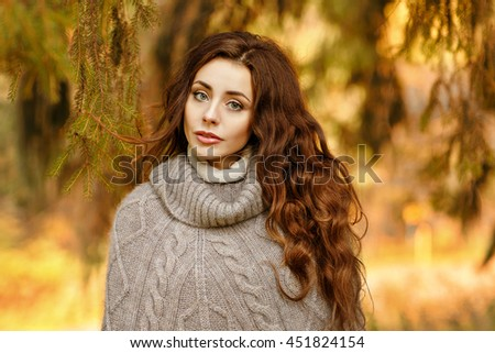 Portrait of a beautiful and a little sad girl with long wavy hair in knit sweater autumn at sunset - stock photo