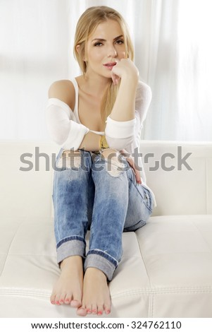 Portrait of a beautiful and attractive young adult sexy and sensuality pretty smile blonde woman posing in blue jeans and white shirt sweater on the white couch - stock photo