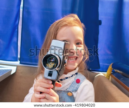 Portrait of a beautiful and confident small girl with camera. Little girl making a film in the camera. - stock photo