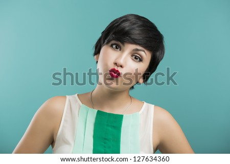 Portrait of a beautiful and fashion woman aganist a blue background - stock photo
