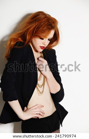 Portrait of a beautiful and sensual girl with red hair in a studio on a white background