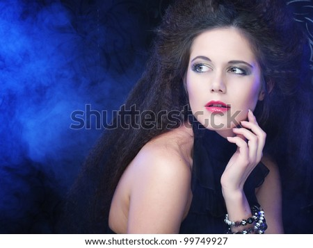 Portrait of a beautiful and sexy brunette woman in smoke