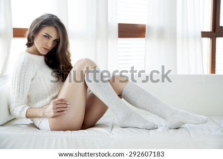Portrait of a beautiful and sexy young adult sensuality attractive pretty brunette woman in white sweater and grey socks on the white sofa in morning sunlight  window on luxury  style hotel apartment