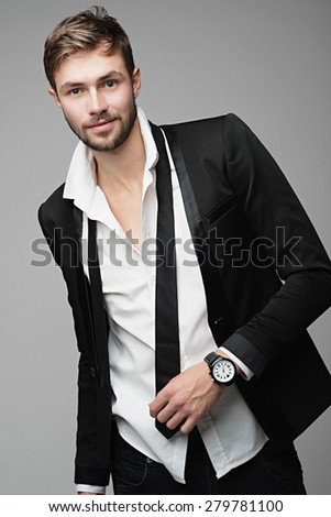 Portrait of a beautiful and stylish men in suit posing in studio - stock photo