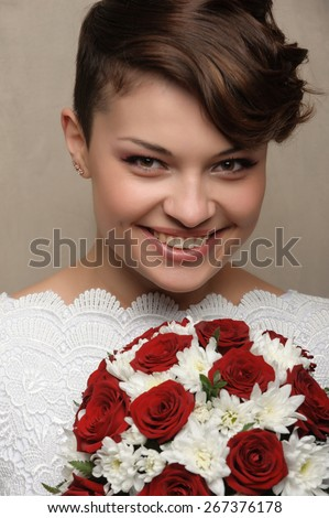 Portrait of a beautiful and very happy young girl with flowers. short-haired brunette hair. widely smiling at the camera - stock photo