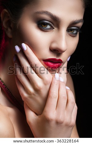portrait of a beautiful and young woman with red lipstick on a black background
