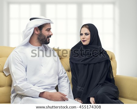 Portrait of a beautiful Arabian muslim couple sitting on the couch in a modern interior