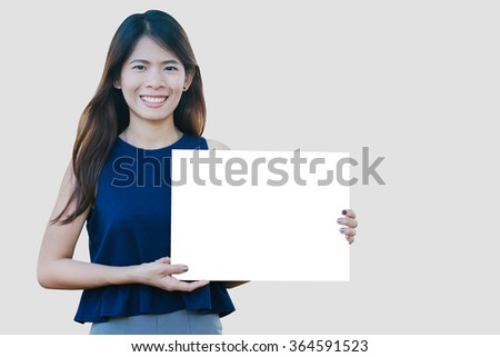 Portrait of a Beautiful asia woman holding a blank signboard over grey background.