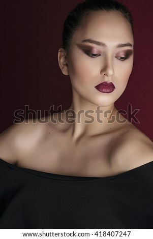 Portrait of a beautiful Asian girl in a black dress, bare shoulders. Bright make-up, red lips and eyes