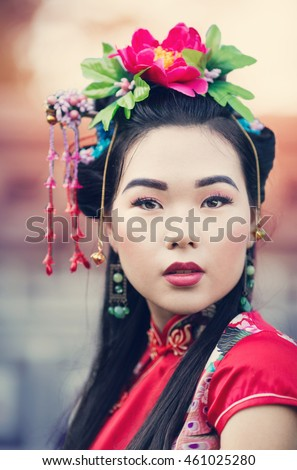 Portrait of a beautiful asian girl in a smart dress with national motifs and professional makeup, closeup, spring garden